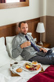Businessman with laptop during breakfast. He is lying on bed. Stock Image