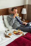 Businessman with laptop during breakfast. He is lying on bed. Royalty Free Stock Photo