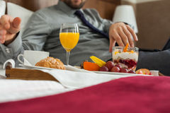 Businessman with laptop during breakfast. He is lying on bed. Stock Photos