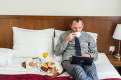 Businessman with laptop during breakfast. He is lying on bed. Royalty Free Stock Image