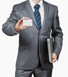 Businessman With Laptop and Business Card. Serious Businessman With Laptop Shows A Business Card Royalty Free Stock Photo