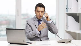 Businessman with laptop calling on phone stock video