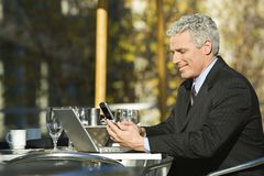 Businessman with laptop and cellphone. Profile of smiling prime adult Caucasian man in suit sitting at patio table outside with laptop and dialing cellphone Royalty Free Stock Image