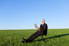 Businessman With Laptop On Chair In Grassy Field Against Sky Stock Photos