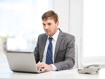 Businessman with laptop computer and documents Stock Images