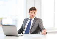 Businessman with laptop computer and documents. Technology, business and office concept - puzzled businessman working with laptop computer and documents royalty free stock photos