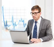Businessman with laptop computer and forex chart Royalty Free Stock Image