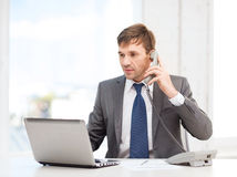 Businessman with laptop computer and phone Royalty Free Stock Images