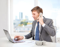 Businessman with laptop computer and phone Royalty Free Stock Photography