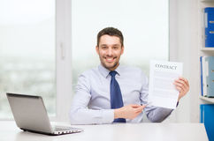 Businessman with laptop and contract at office Royalty Free Stock Photo