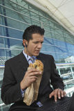 Businessman With Laptop Eating Bagel Royalty Free Stock Photo