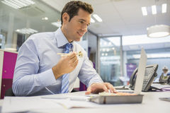 Businessman with laptop eating sushi on his desk Royalty Free Stock Images