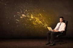 Businessman with laptop and energy explosion on background Stock Photography