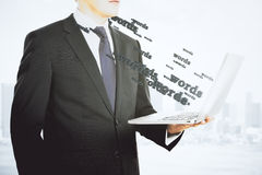 Businessman with laptop and flying words Stock Photography