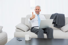 Businessman with laptop gesturing thumbs up at home Stock Images