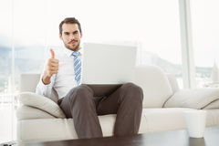Businessman with laptop gesturing thumbs up in living room Stock Photos