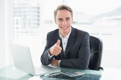 Businessman with laptop gesturing thumbs up at office desk Royalty Free Stock Images
