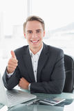 Businessman with laptop gesturing thumbs up at office desk Stock Image