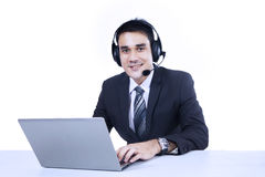 Businessman with laptop and headset Royalty Free Stock Image