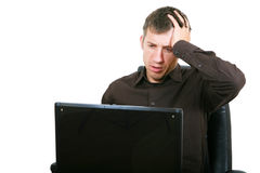 Businessman with laptop, holding head in hands Royalty Free Stock Image