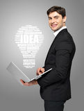 Businessman with laptop and lamp Royalty Free Stock Photos