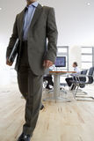 Businessman with laptop leaving conference room Stock Photo