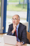 Businessman With Laptop Looking Up At Desk Stock Photo