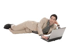 Businessman with laptop lying Royalty Free Stock Photography