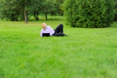 Businessman with laptop lying on green grass Royalty Free Stock Image