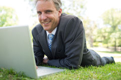 Businessman with laptop lying in park. Portrait of smiling businessman with laptop lying on grass in park Stock Photos