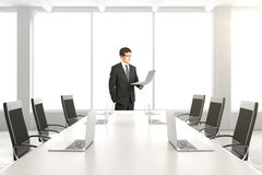 Businessman with laptop in modern white conference room with tab Stock Images