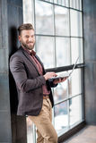 Businessman with laptop near the window Royalty Free Stock Images