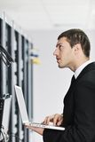 Businessman with laptop in network server room Royalty Free Stock Photography