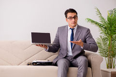 The businessman with laptop notebook sitting in sofa Stock Photos