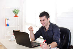 Businessman with laptop at office desk Stock Photo