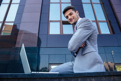 Businessman with laptop outdoors Stock Image
