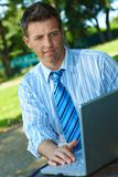 Businessman with laptop in park Royalty Free Stock Images