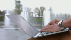 Businessman with a laptop in the park stock footage