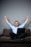 Businessman with laptop raises arms Stock Images