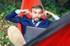 Businessman with laptop relaxs in a hammock on nature. He talking on video chat and doing funny faces with his tongue hanging out stock image