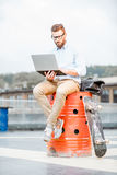 Businessman with laptop on the rooftop Royalty Free Stock Image