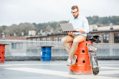 Businessman with laptop on the rooftop Stock Photo