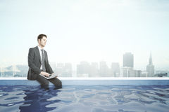 Businessman with laptop in rooftop pool Stock Photography