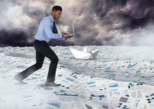 Businessman on laptop in sea of documents under sky clouds with paper boats. Digital composite of Businessman on laptop in sea of documents under sky clouds with Stock Photo