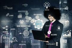 Businessman with a laptop and SEO button Royalty Free Stock Image