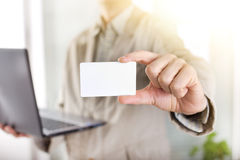 Businessman with laptop showing business card Royalty Free Stock Photography