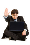 Businessman with laptop showing stop gesture Stock Image