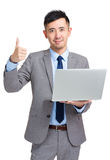 Businessman with laptop showing thumb up Stock Photography