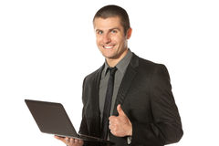 Businessman with laptop showing thumps up sign Royalty Free Stock Images