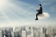 Businessman with laptop sits on the cloud Stock Photos